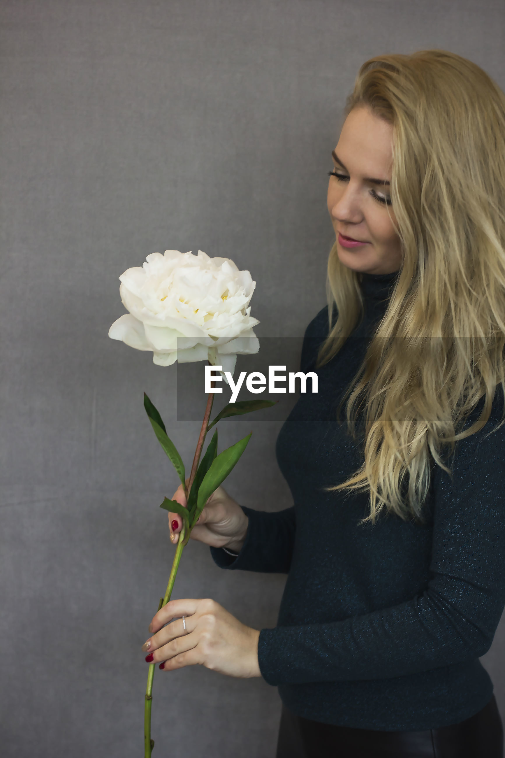 Woman holding white flower against gray wall