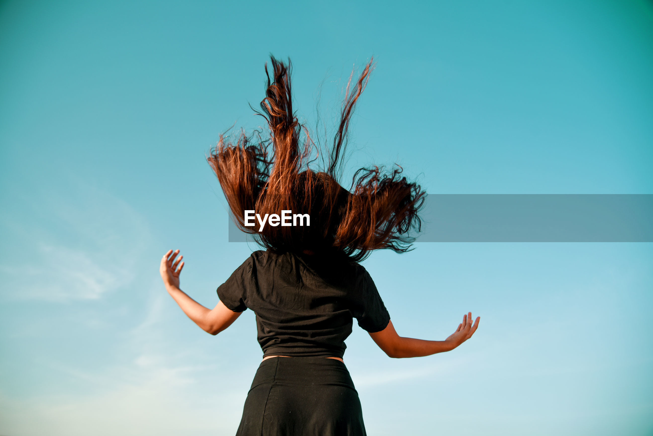 Rear view of woman tossing hair against sky