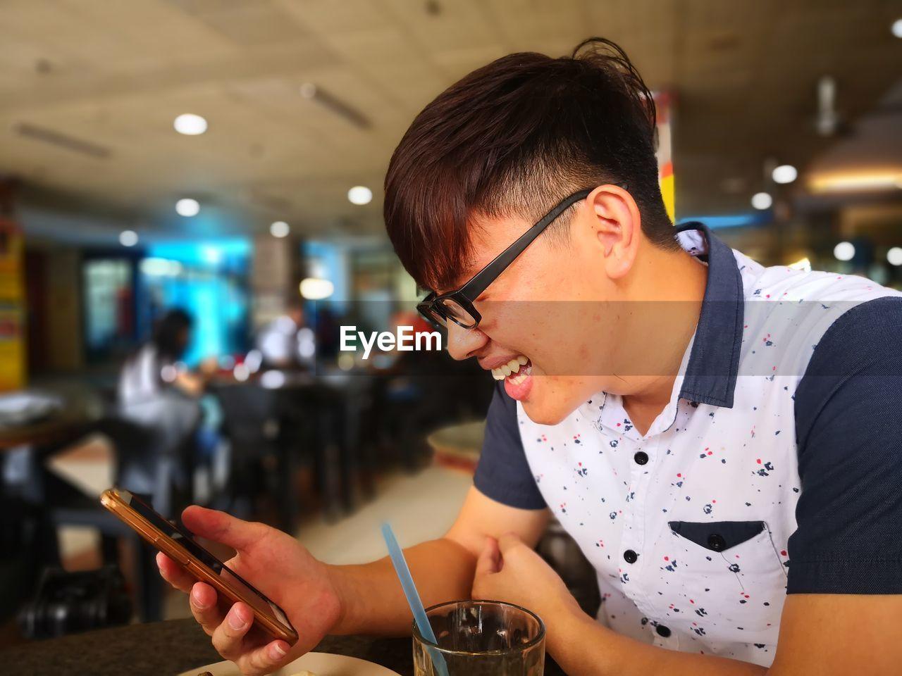 Smiling man using mobile phone while sitting at restaurant