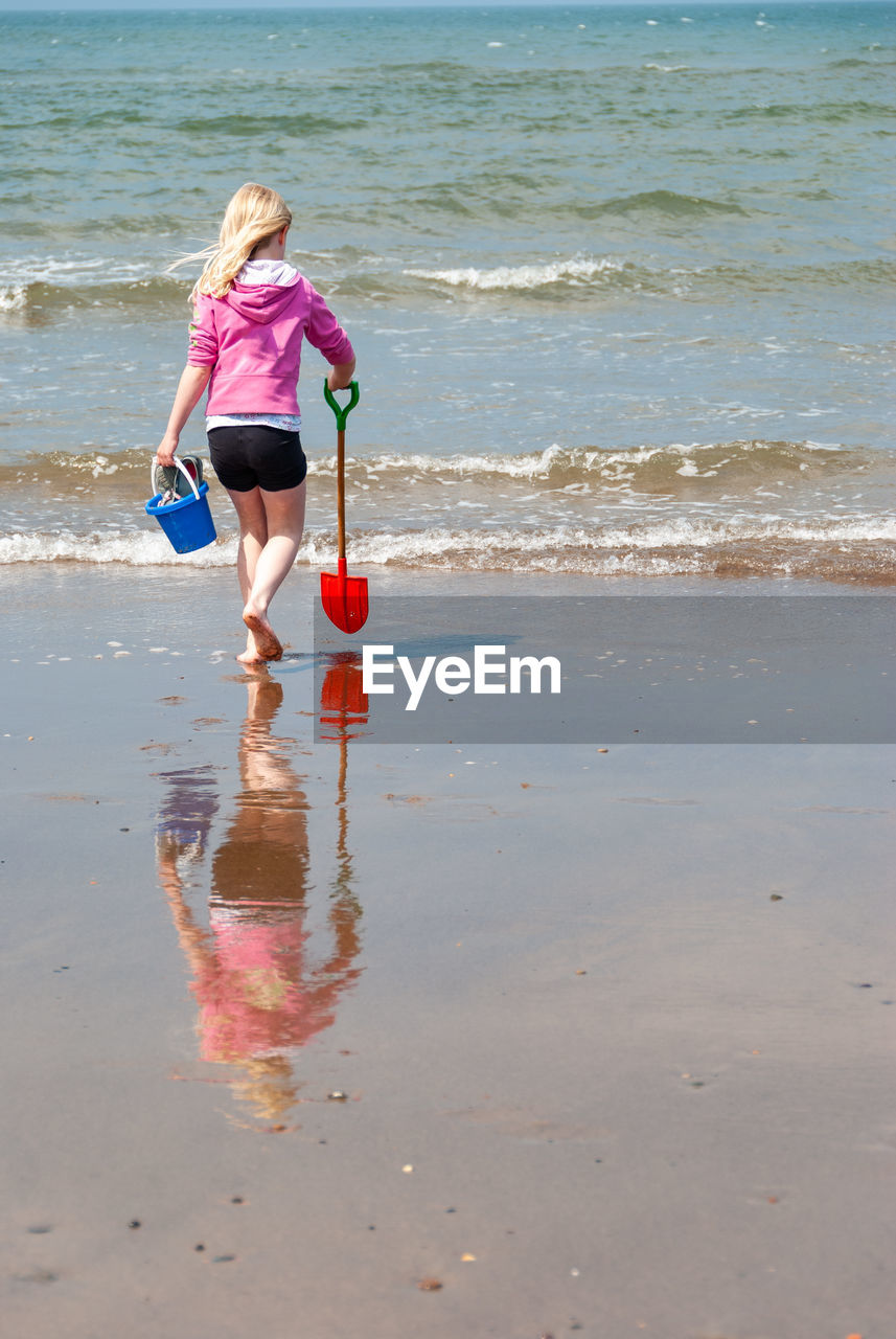 Rear view of girl with toys walking at beach during sunny day