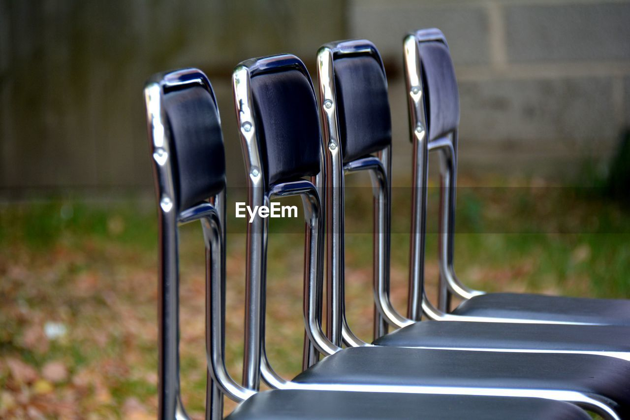 metal, no people, focus on foreground, in a row, empty, day, absence, silver colored, close-up, steel, seat, nature, shiny, outdoors, side by side, still life, order, chair, black color, stainless steel, alloy