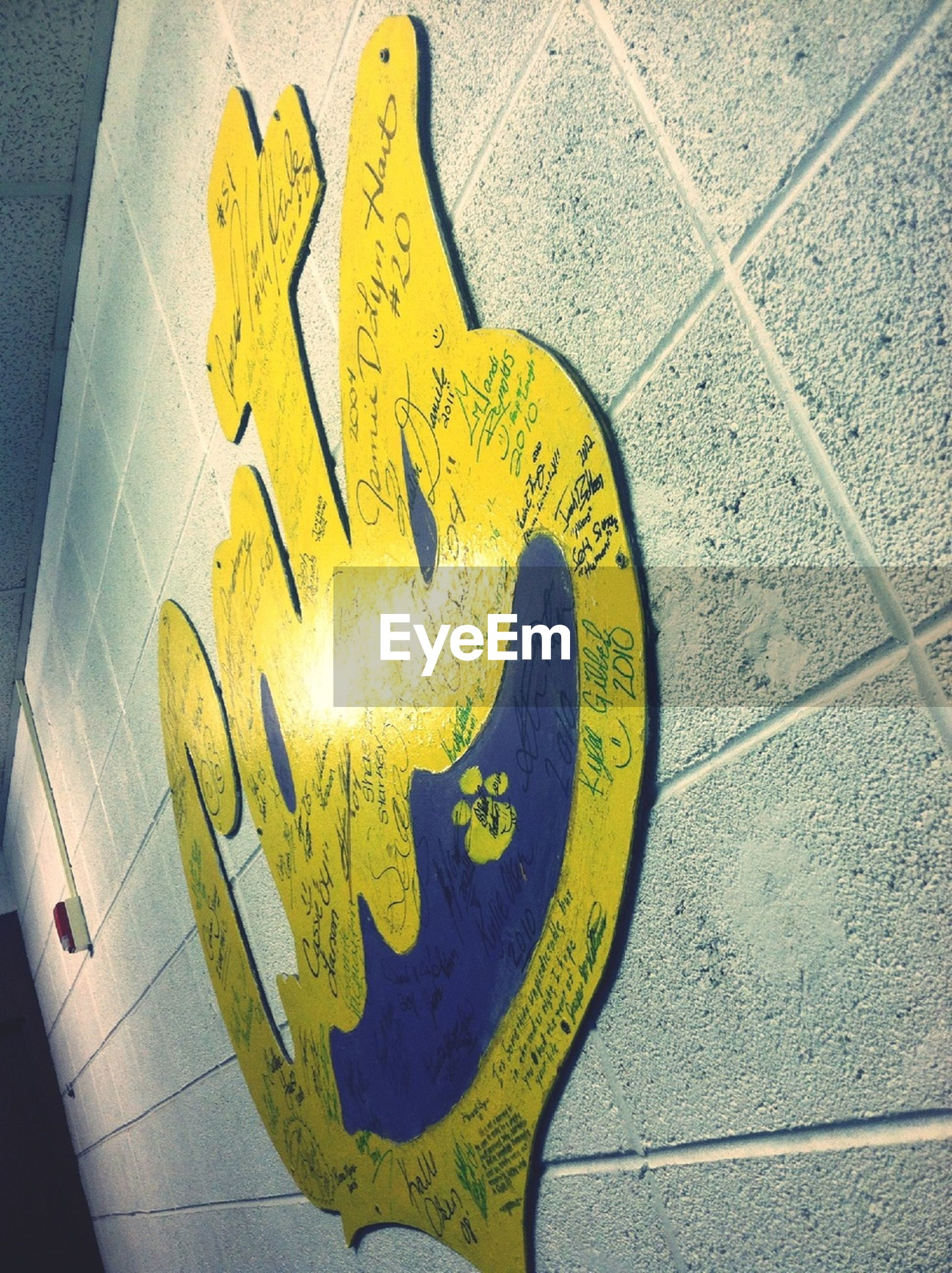 art, creativity, art and craft, human representation, animal representation, wall - building feature, graffiti, craft, indoors, yellow, text, high angle view, close-up, communication, wall, anthropomorphic face, sculpture, ideas
