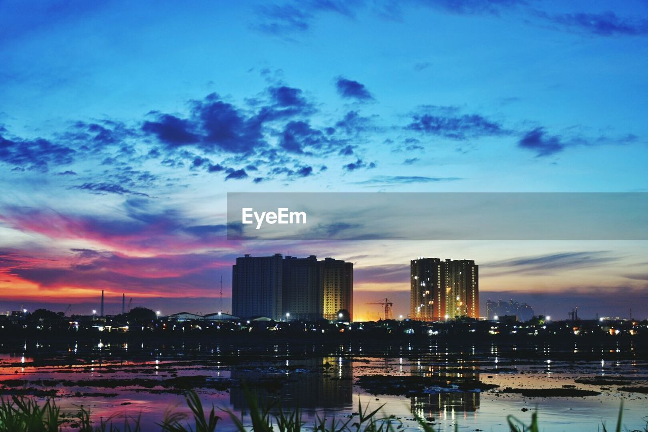 building exterior, architecture, sky, built structure, skyscraper, sunset, cloud - sky, cityscape, city, urban skyline, water, waterfront, no people, illuminated, travel destinations, outdoors, modern, nature, day