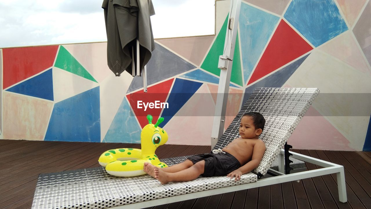 Full length of shirtless boy lying with inflatable ring on lounge chair
