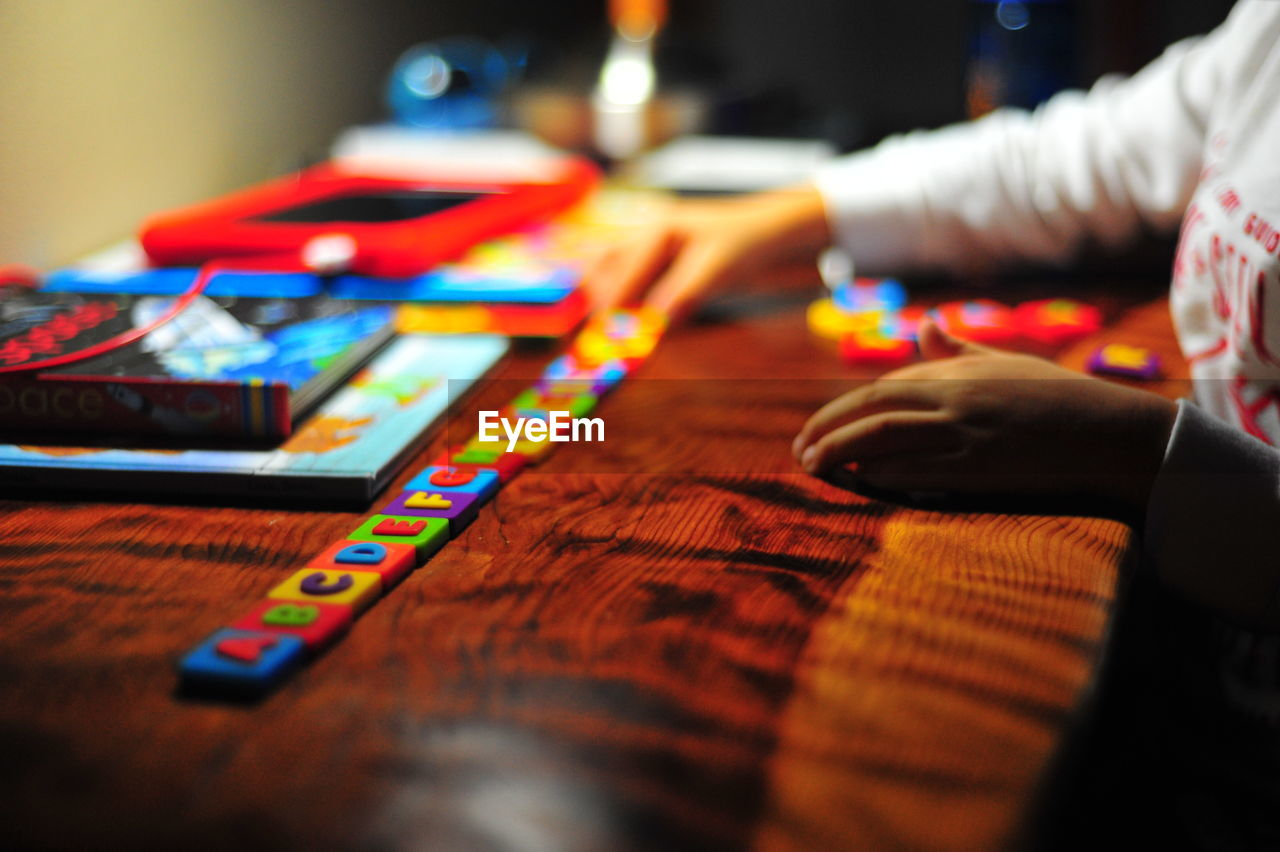 Cropped Image Of Child Hand Playing With Alphabet Blocks On Table