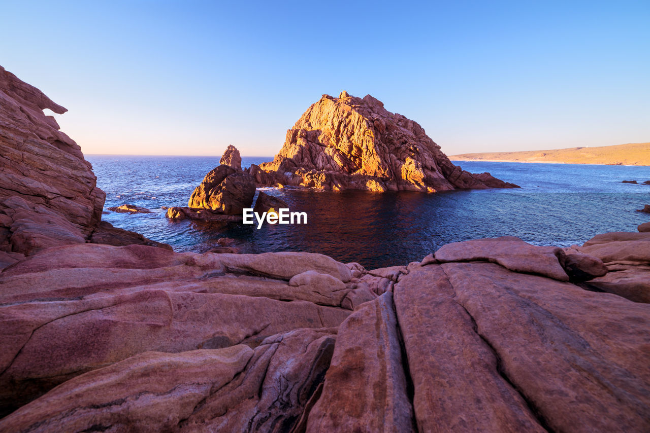 water, rock, sky, sea, rock - object, solid, rock formation, beauty in nature, scenics - nature, land, clear sky, nature, tranquility, horizon over water, tranquil scene, horizon, blue, non-urban scene, beach, no people, outdoors, stack rock, eroded