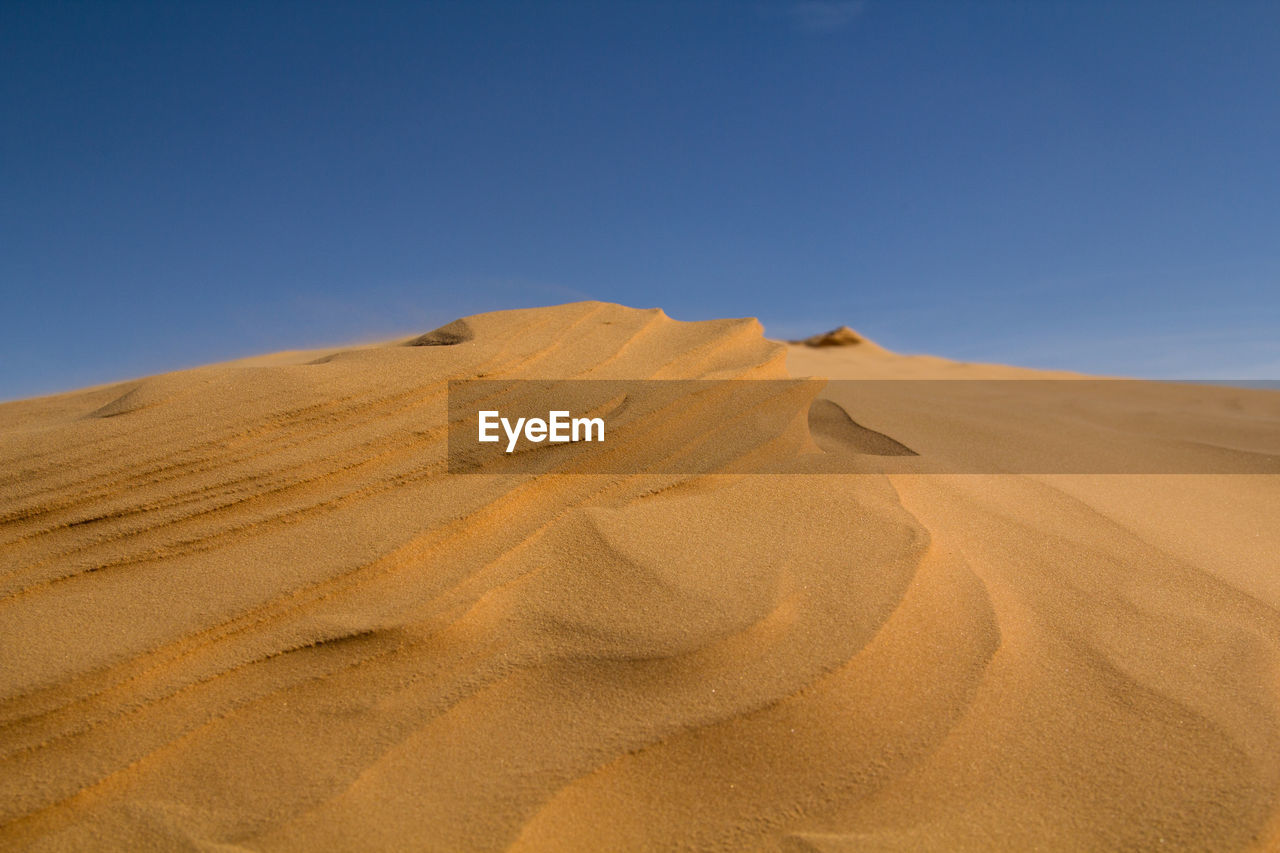 sand dune, desert, nature, sand, arid climate, landscape, clear sky, blue, extreme terrain, tranquil scene, beauty in nature, day, outdoors, tranquility, scenics, physical geography, sky, no people