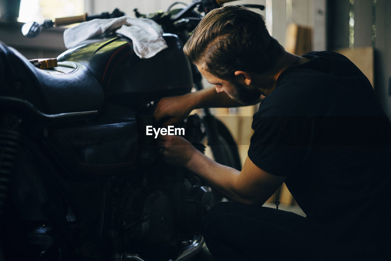 mode of transportation, land vehicle, transportation, one person, real people, occupation, motor vehicle, car, men, indoors, adult, working, auto repair shop, focus on foreground, casual clothing, young men, young adult, shopping, lifestyles, garage, mechanic, care