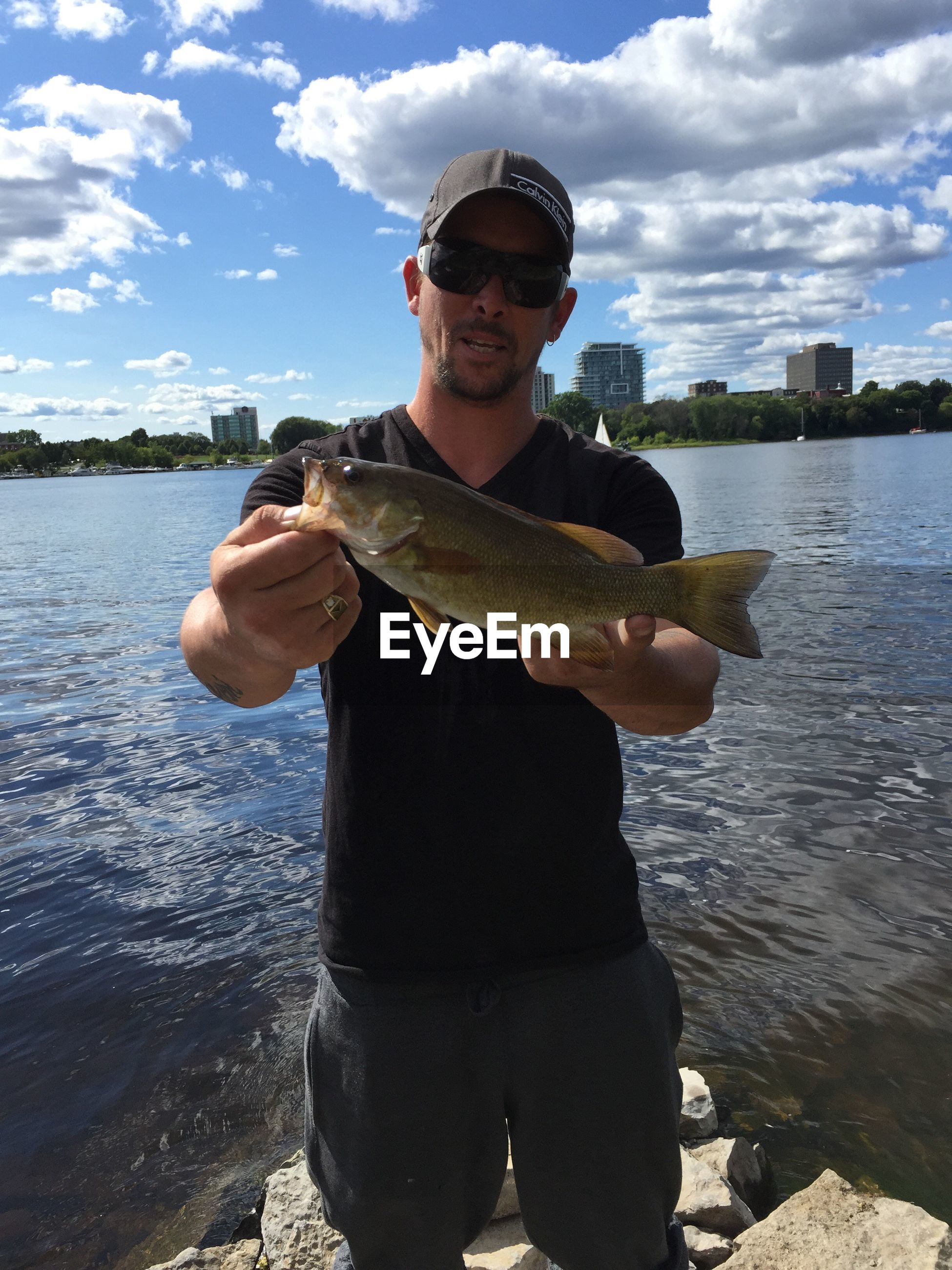 PORTRAIT OF MAN HOLDING FISH AT LAKE