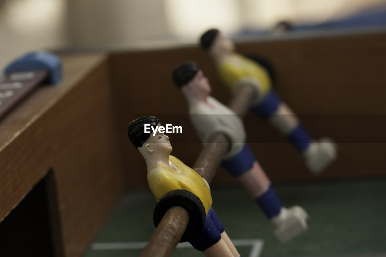 human representation, male likeness, representation, figurine, focus on foreground, indoors, sport, art and craft, creativity, team sport, close-up, still life, no people, soccer, toy, sculpture, competition, craft, table, female likeness