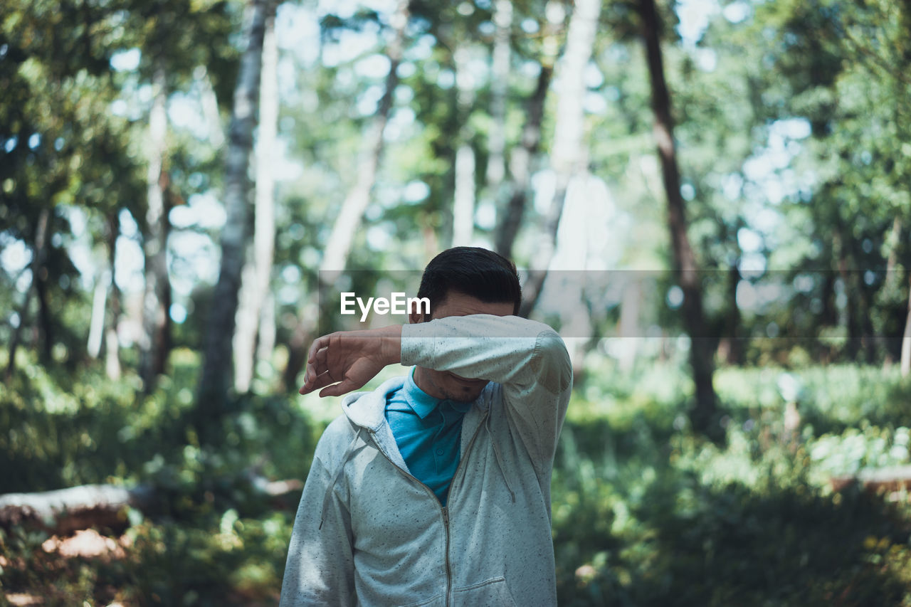 Man Covering Eyes In Forest