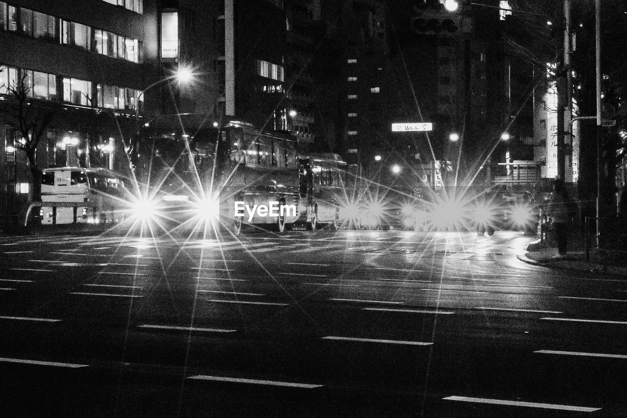night, illuminated, city, street, architecture, transportation, building exterior, mode of transportation, road, built structure, motor vehicle, motion, car, headlight, blurred motion, city life, street light, city street, land vehicle, light beam, outdoors, nightlife
