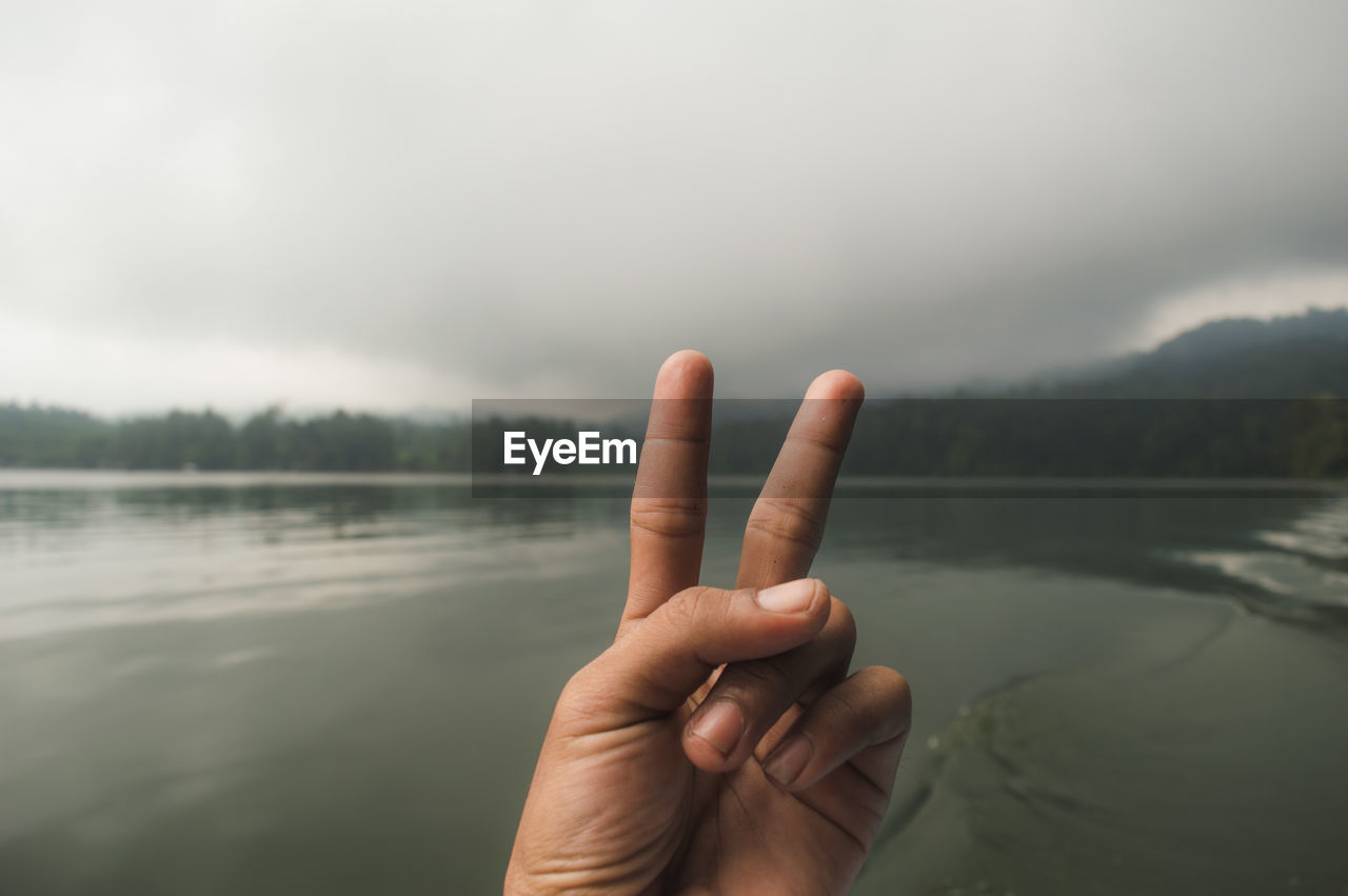 Cropped Hand Gesturing Peace Sign By Lake Against Cloudy Sky