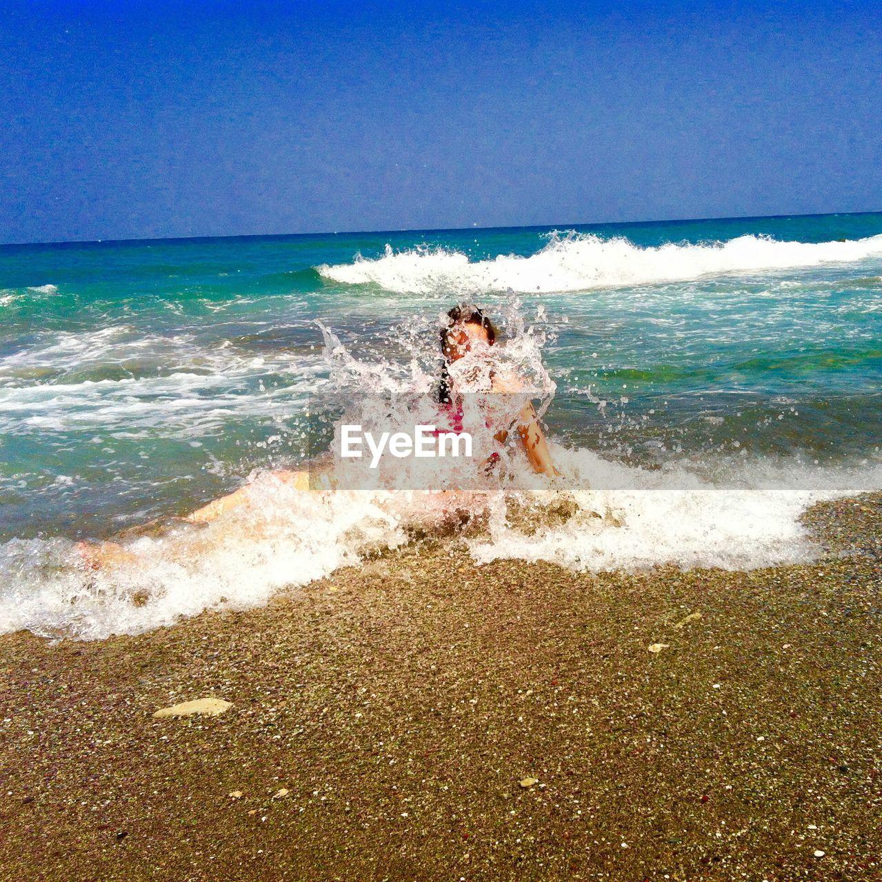 Woman Sitting On Splashing Sea Waves At Beach Against Sky