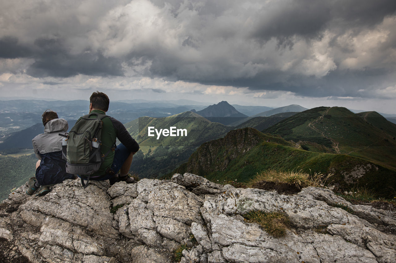 REAR VIEW OF MEN LOOKING AT MOUNTAIN AGAINST SKY