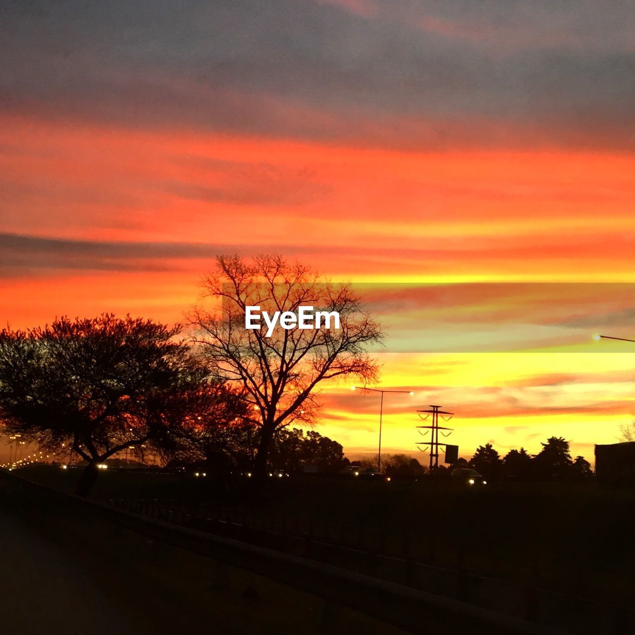 sunset, orange color, tree, silhouette, sky, dramatic sky, cloud - sky, no people, nature, beauty in nature, scenics, tranquil scene, transportation, road, tranquility, outdoors, electricity pylon, landscape, day