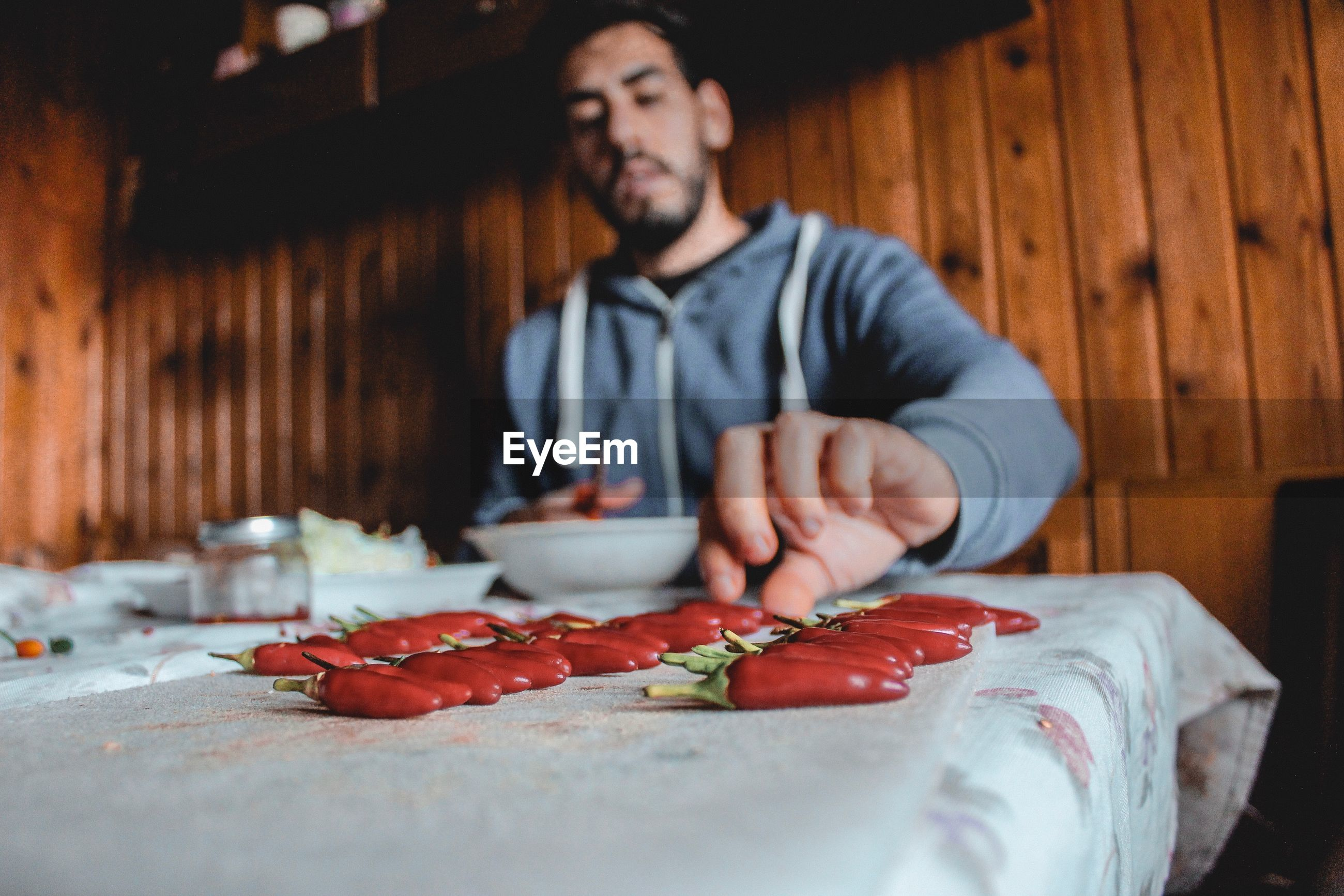 Man having red chili pepper at table in restaurant