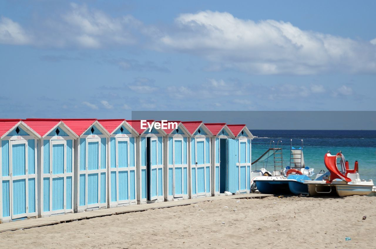 water, beach, sea, sky, land, cloud - sky, beach hut, horizon over water, sand, built structure, nature, architecture, horizon, hut, scenics - nature, beauty in nature, no people, multi colored, day, outdoors, turquoise colored