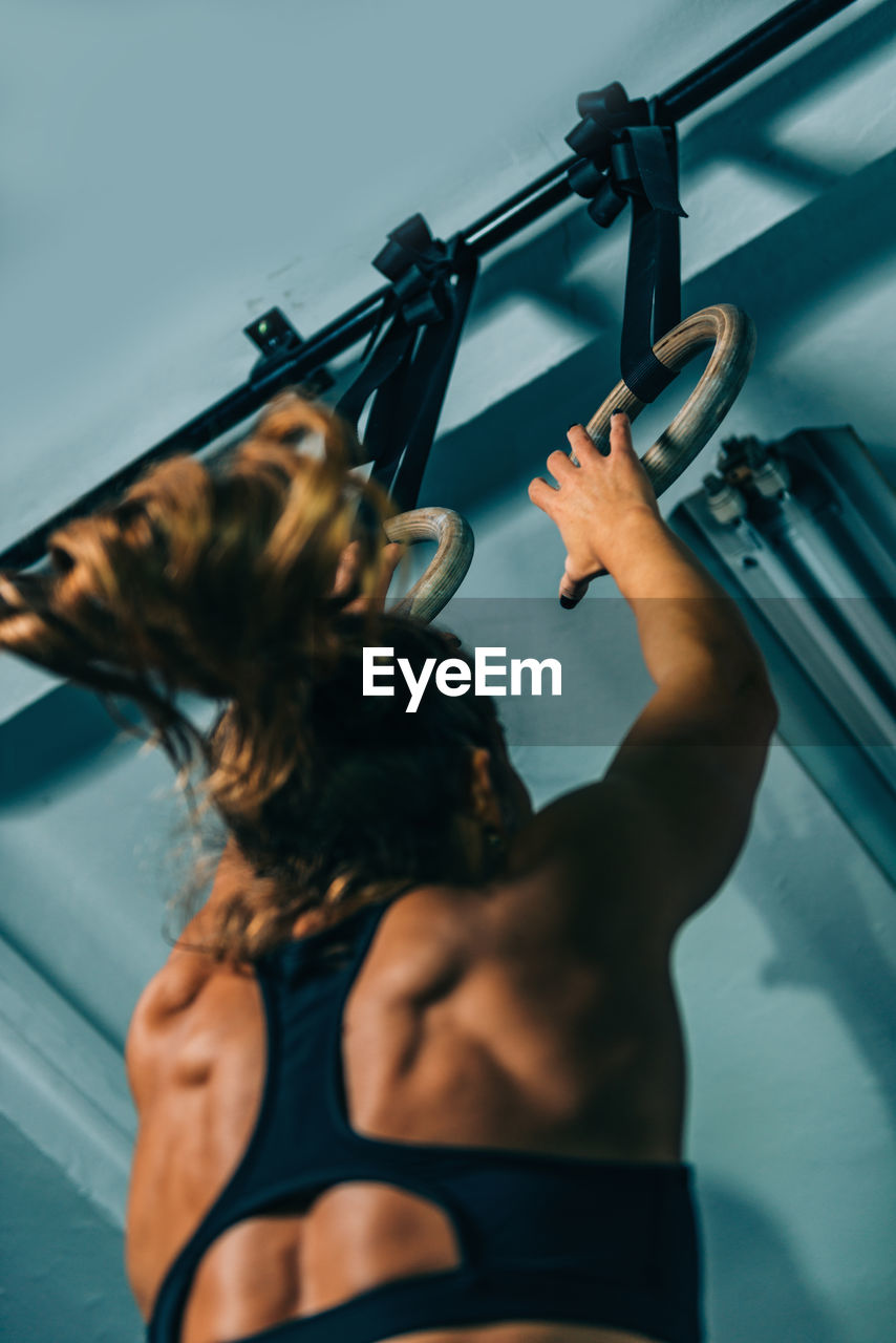 one person, real people, lifestyles, indoors, women, adult, rear view, hairstyle, strength, holding, hair, leisure activity, sport, muscular build, waist up, young adult, clothing, wall - building feature, nature