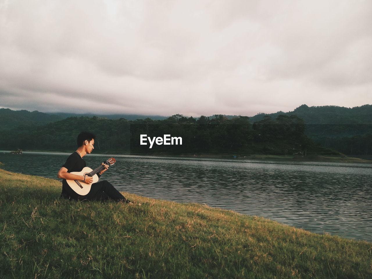 Man playing guitar at lakeshore against sky
