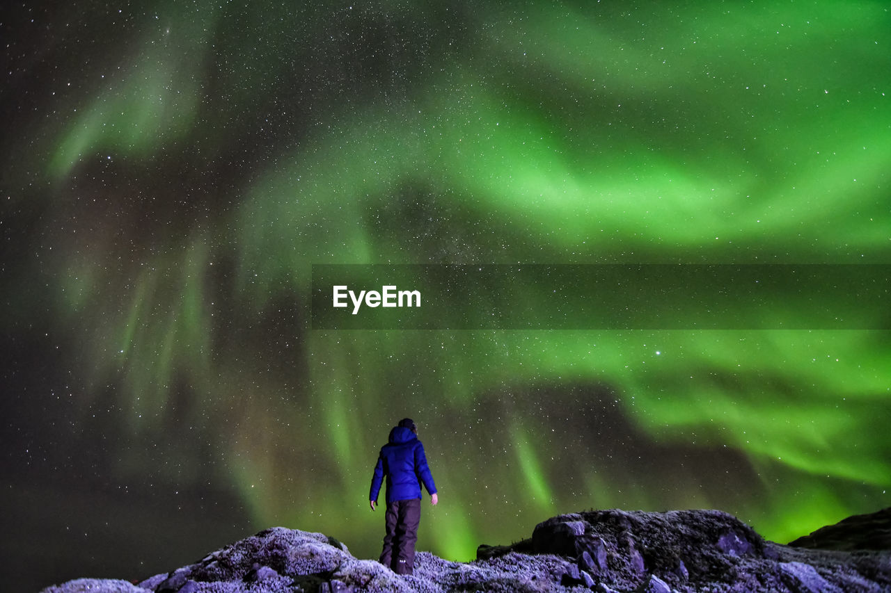 Rear view of person standing on rock against northern lights at night