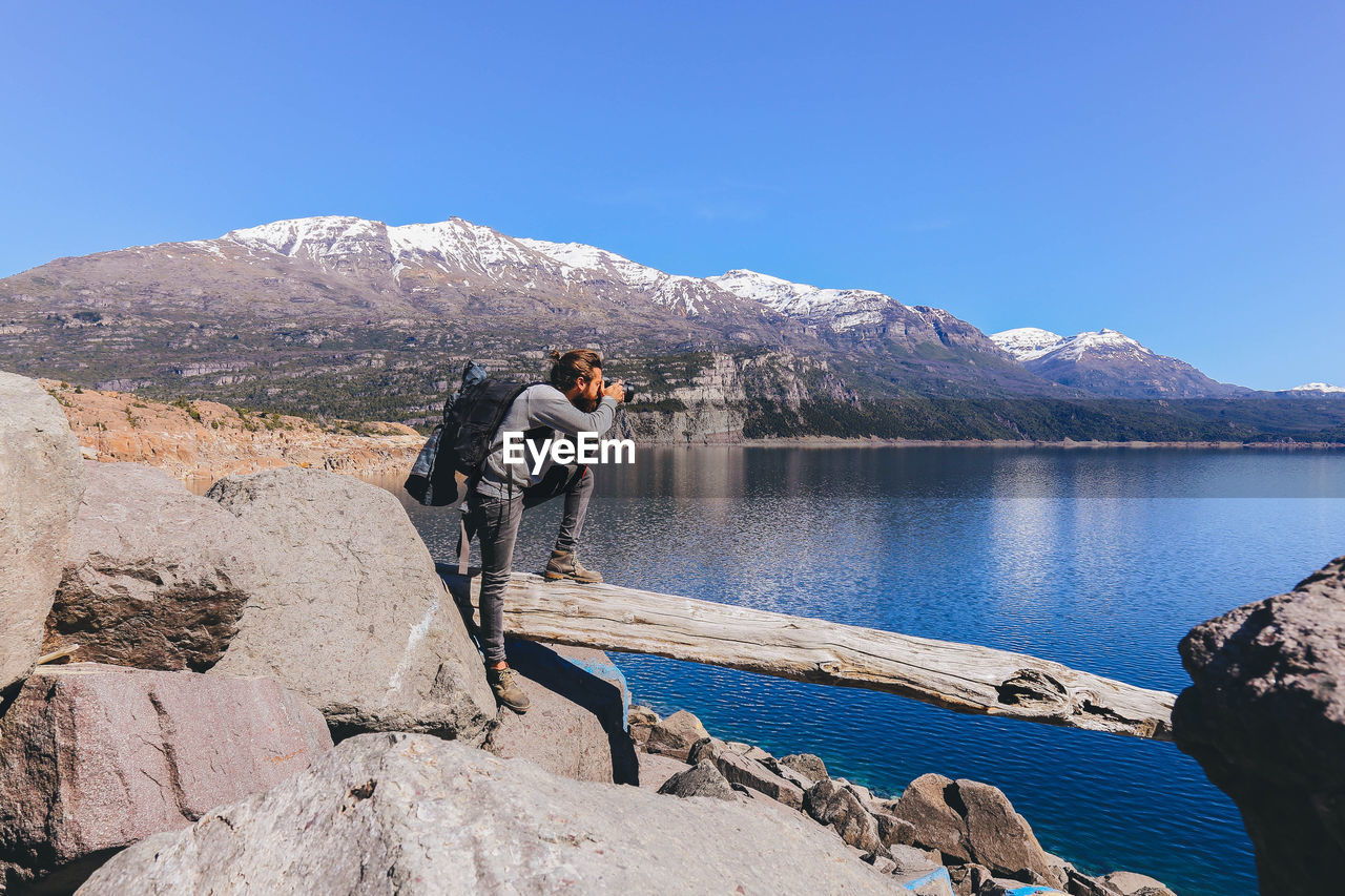 Man photographing lake against sky