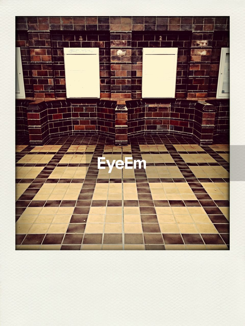 Tiled floor against brick wall