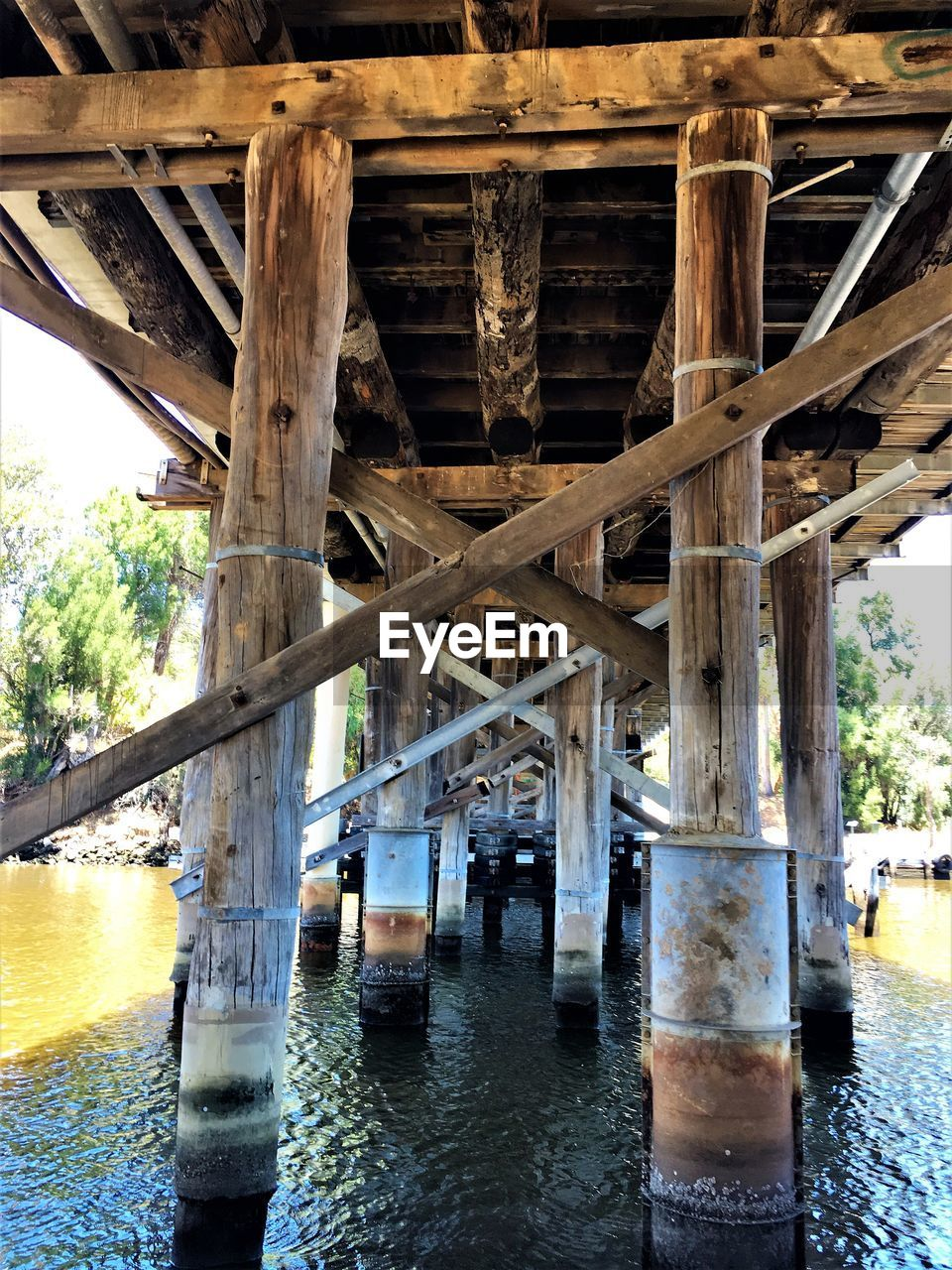 water, bridge - man made structure, connection, below, underneath, architecture, day, river, built structure, outdoors, architectural column, waterfront, nature, no people, under