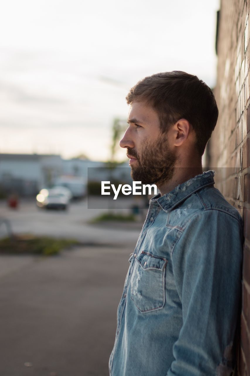 standing, one person, young adult, casual clothing, facial hair, focus on foreground, young men, real people, lifestyles, beard, leisure activity, looking, side view, transportation, waist up, looking away, day, motor vehicle, outdoors, contemplation