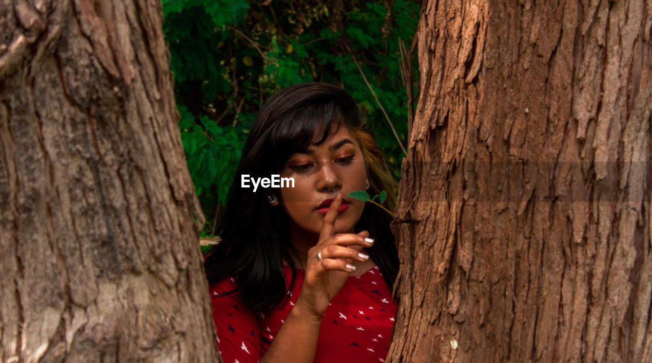 Woman by tree trunk in forest