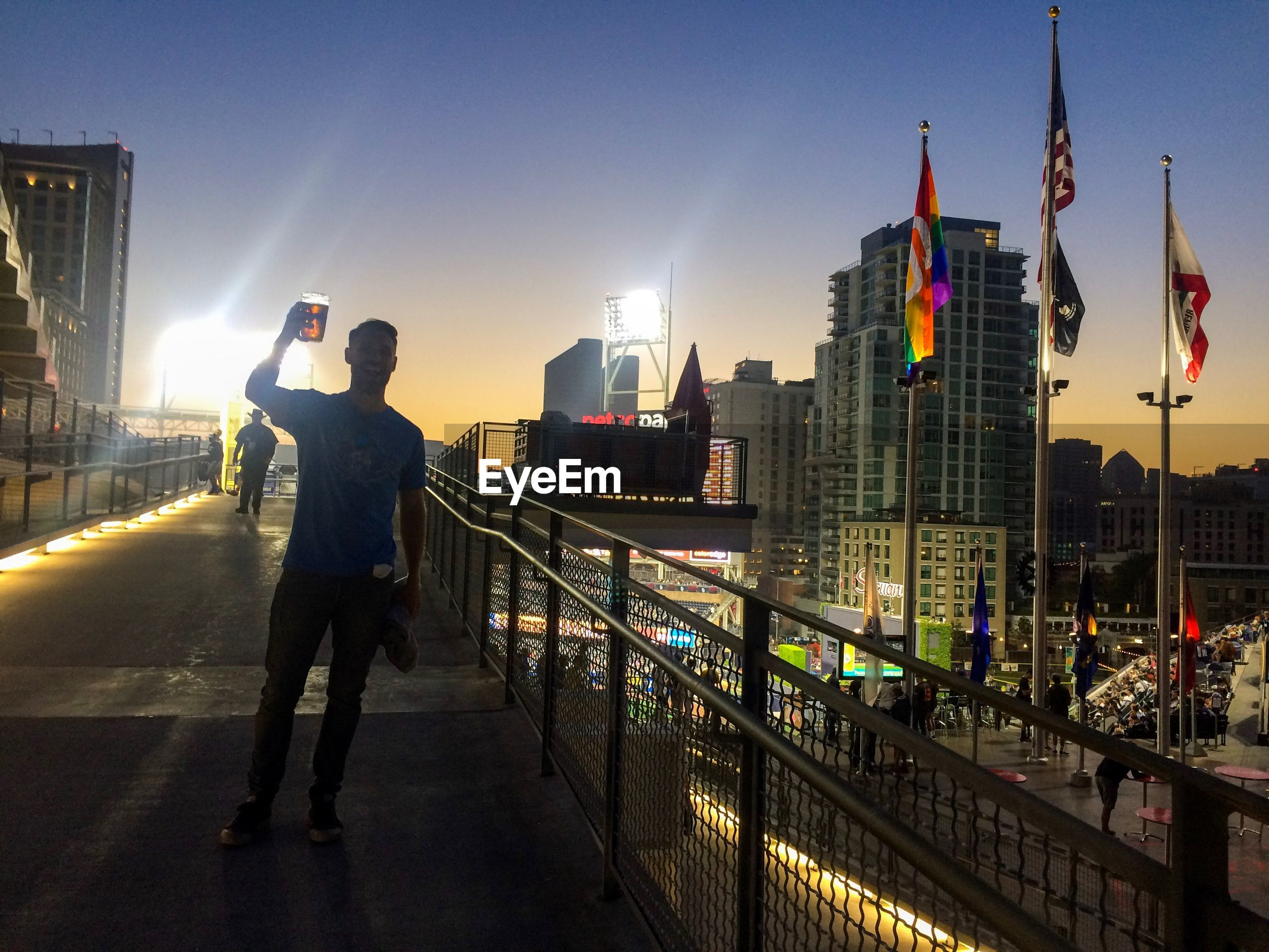 FULL LENGTH OF MAN STANDING ON ILLUMINATED CITY AGAINST CLEAR SKY