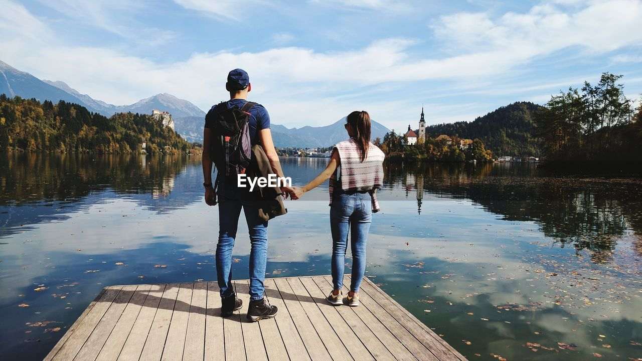 Rear View Of Couple Standing On Pier By Lake Against Sky