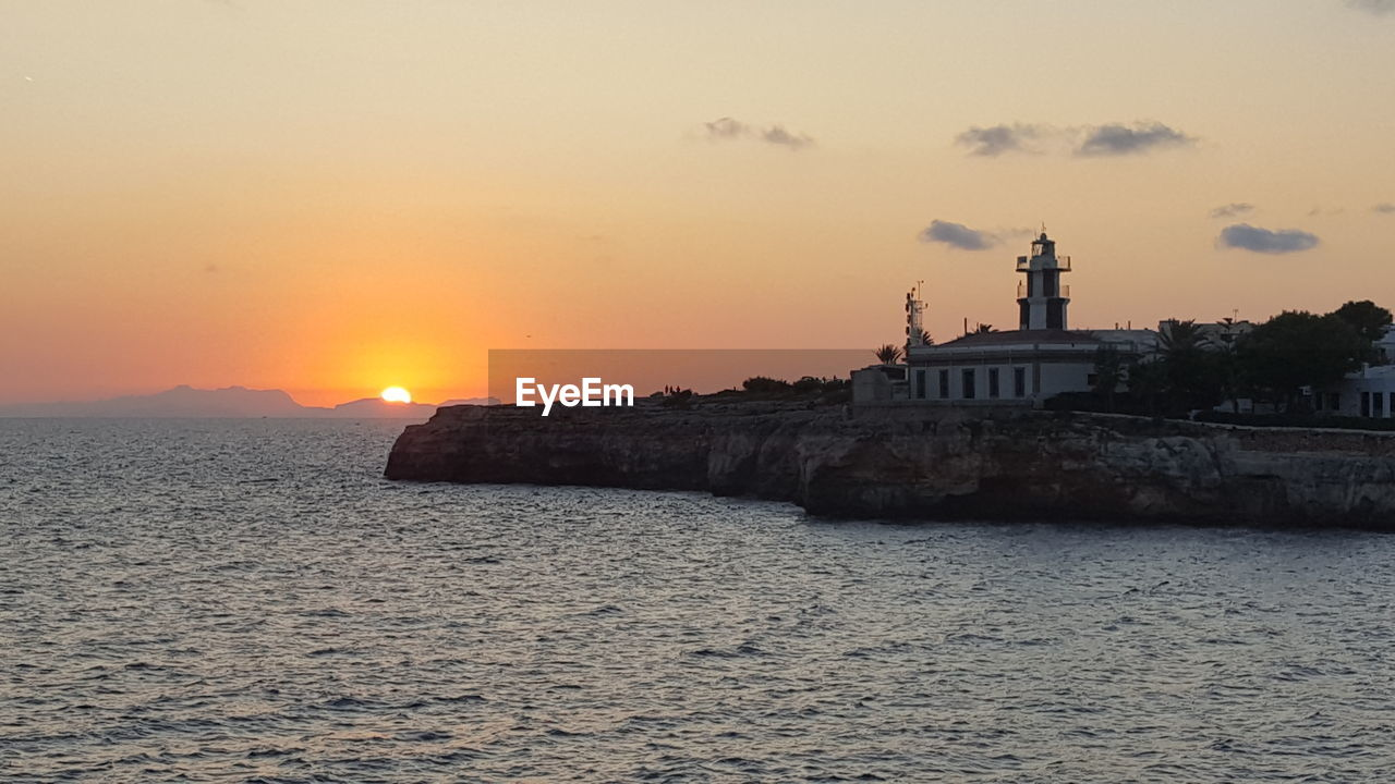 sunset, sea, water, nature, beauty in nature, sky, scenics, sun, lighthouse, no people, architecture, tranquility, built structure, waterfront, building exterior, outdoors, horizon over water, day