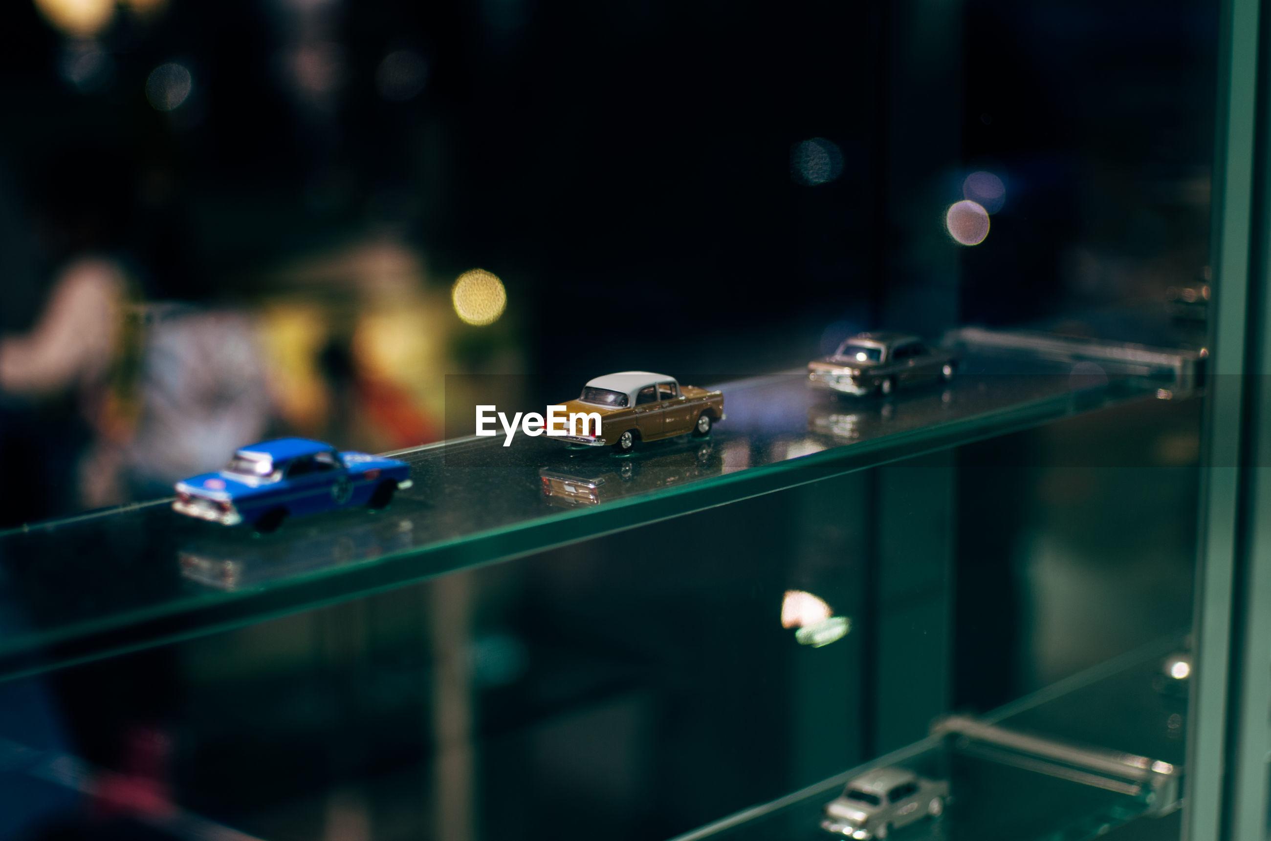 Toy cars on glass shelf