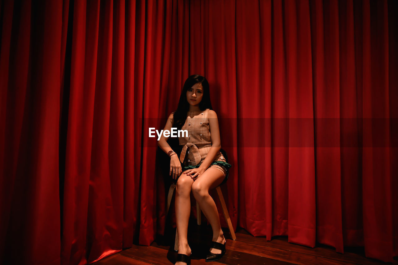 Full Length Of Woman Sitting Against Red Curtain