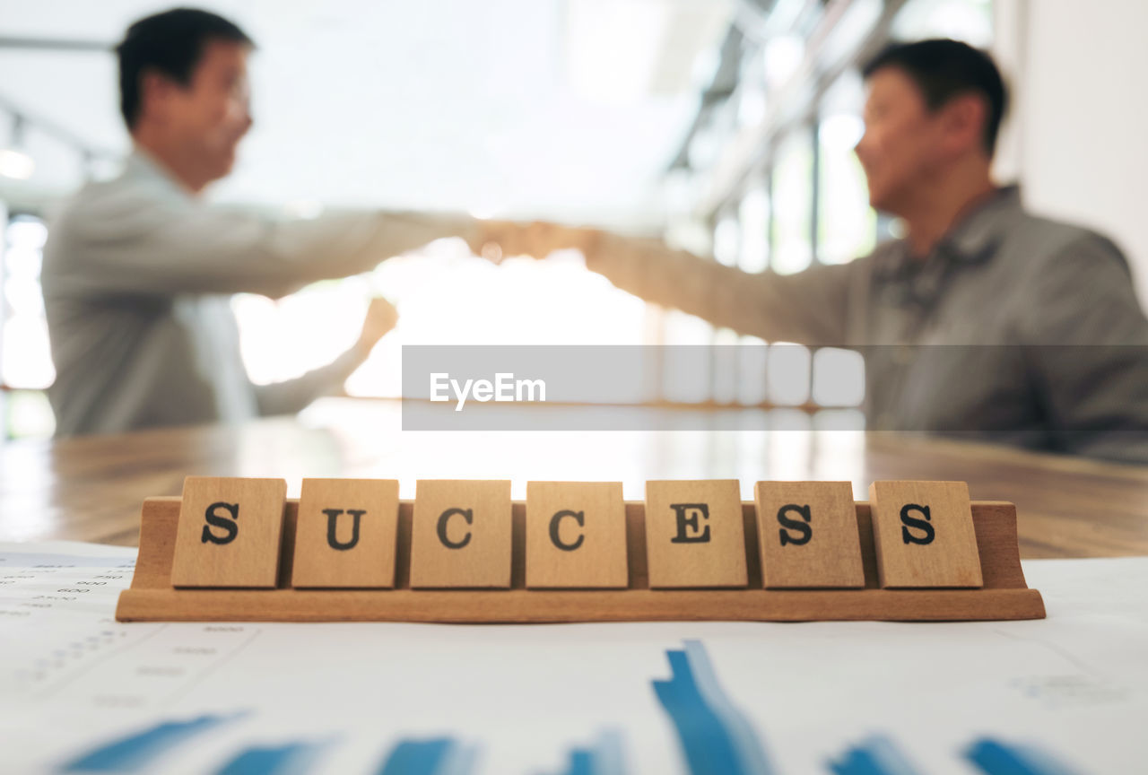 Businessmen Bumping Fists With Success Text In Foreground At Office