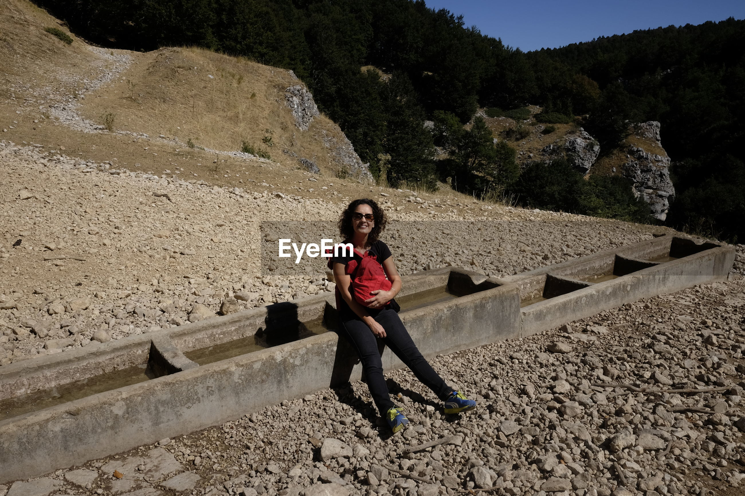 Full length of woman sitting on retaining wall against mountain during sunny day