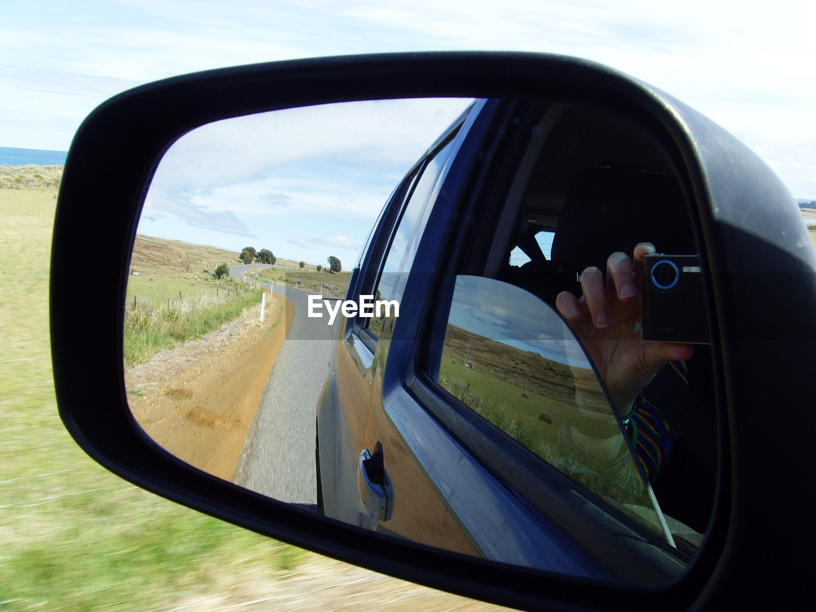 Cropped hand of man photographing while reflecting on side-view mirror