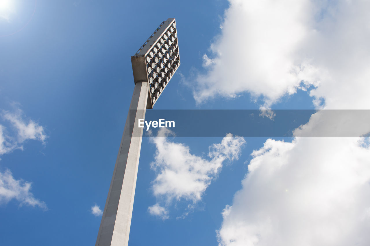 cloud - sky, low angle view, sky, day, blue, nature, no people, sunlight, lighting equipment, outdoors, tall - high, technology, built structure, architecture, fuel and power generation, white color, floodlight, tower, sunny, street light, directly below