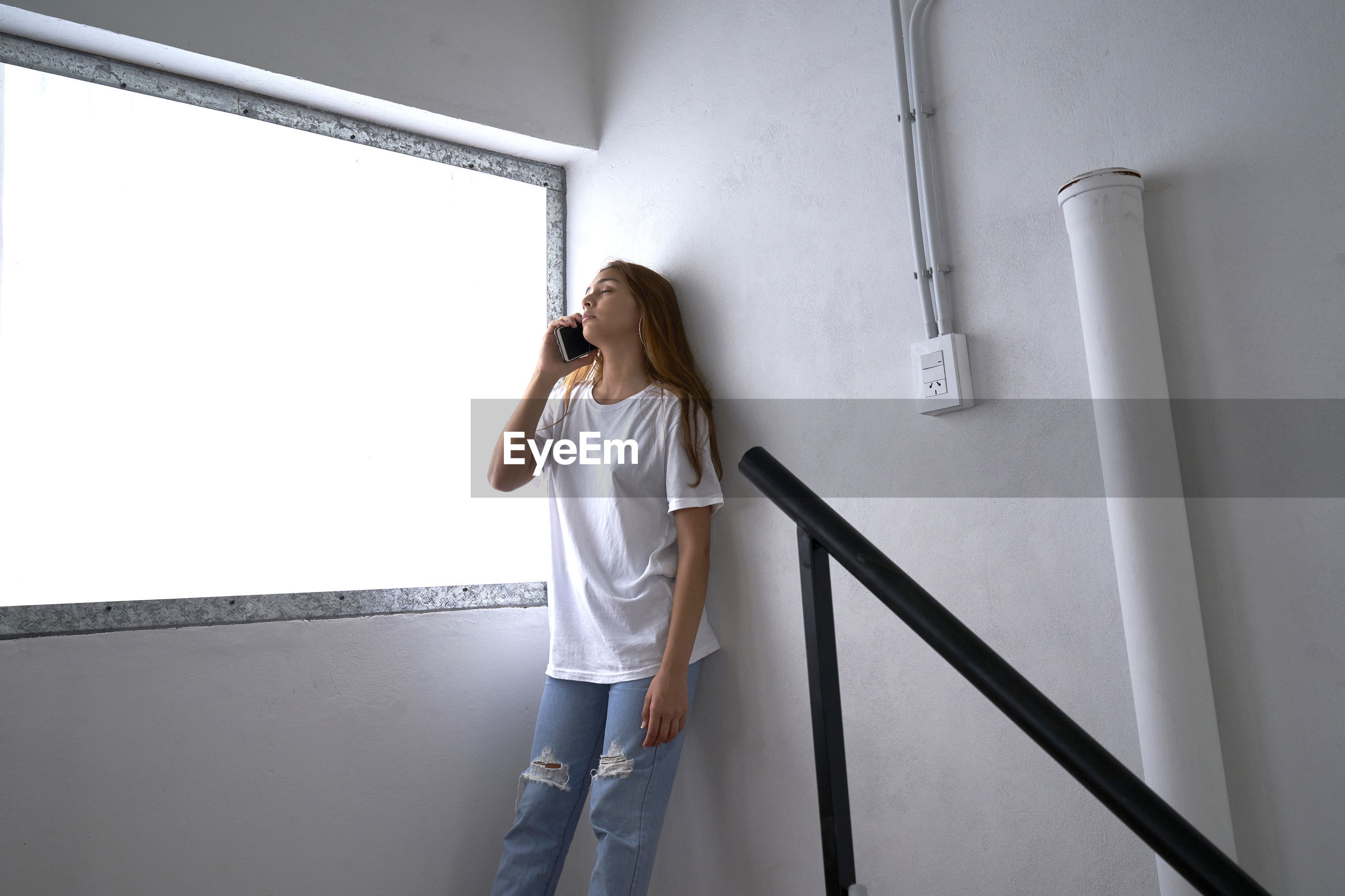 Young latin woman smiles while talking on the cell phone inside her home