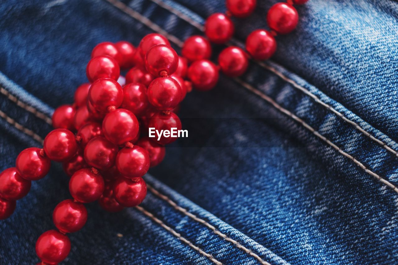 jeans, close-up, textile, fruit, healthy eating, blue, no people, red, indoors, food and drink, food, berry fruit, denim, large group of objects, wellbeing, still life, focus on foreground, casual clothing, bead, wood - material, personal accessory