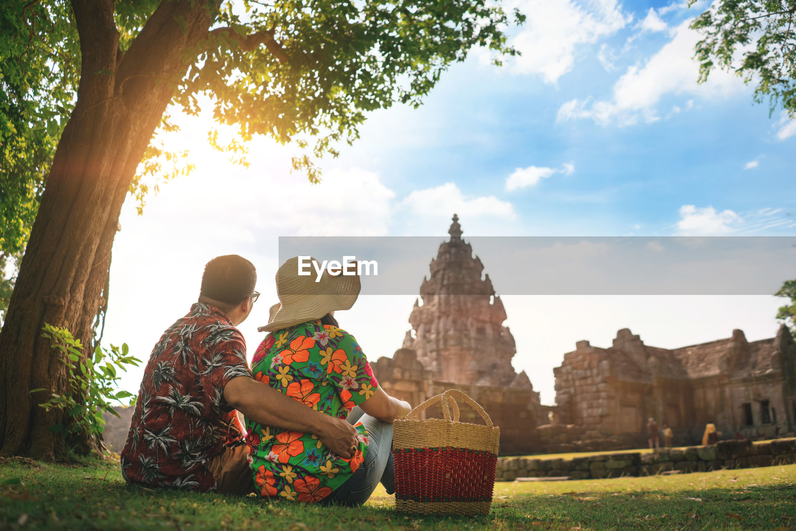 Rear view of couple sitting on grassy field against sky