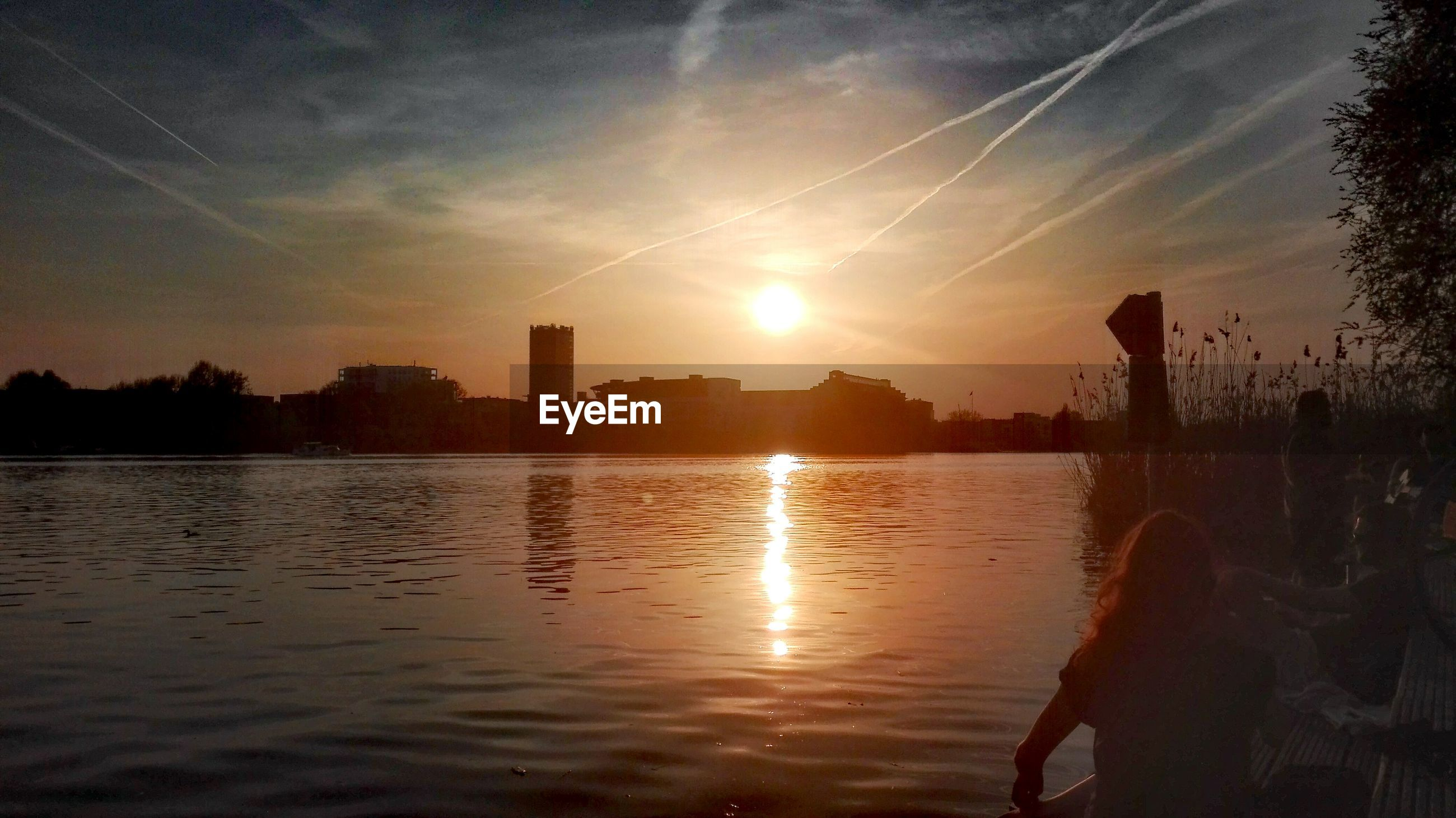 Rear view of woman standing by river against sky during sunset