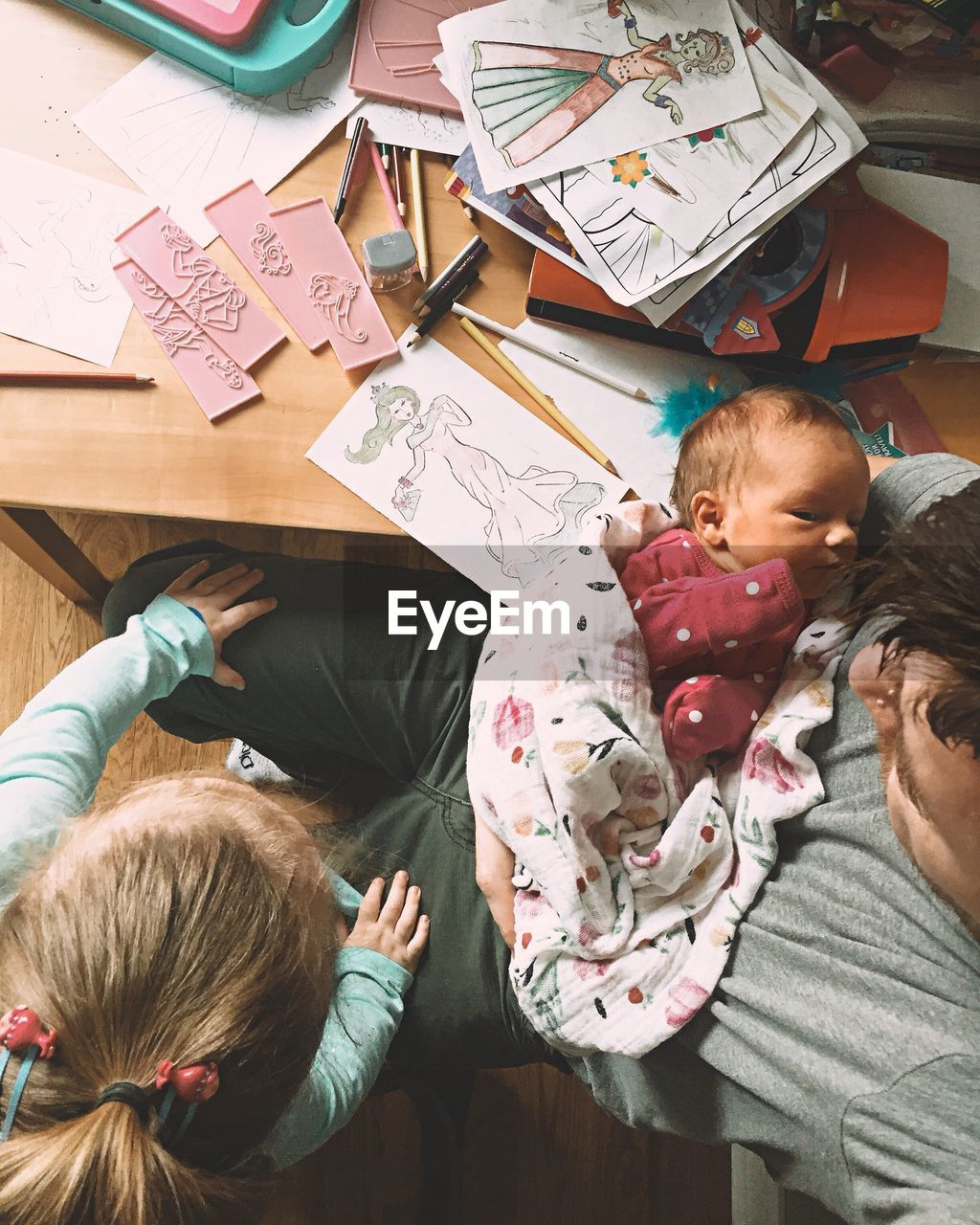 real people, childhood, togetherness, indoors, three people, family, mother, high angle view, love, family with one child, bonding, girls, lifestyles, leisure activity, boys, happiness, women, day, people