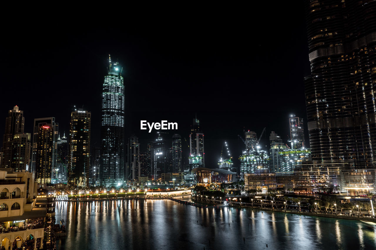 building exterior, architecture, built structure, night, city, illuminated, building, office building exterior, water, tall - high, skyscraper, modern, cityscape, urban skyline, tower, sky, river, landscape, travel destinations, no people, outdoors, financial district, spire, nightlife