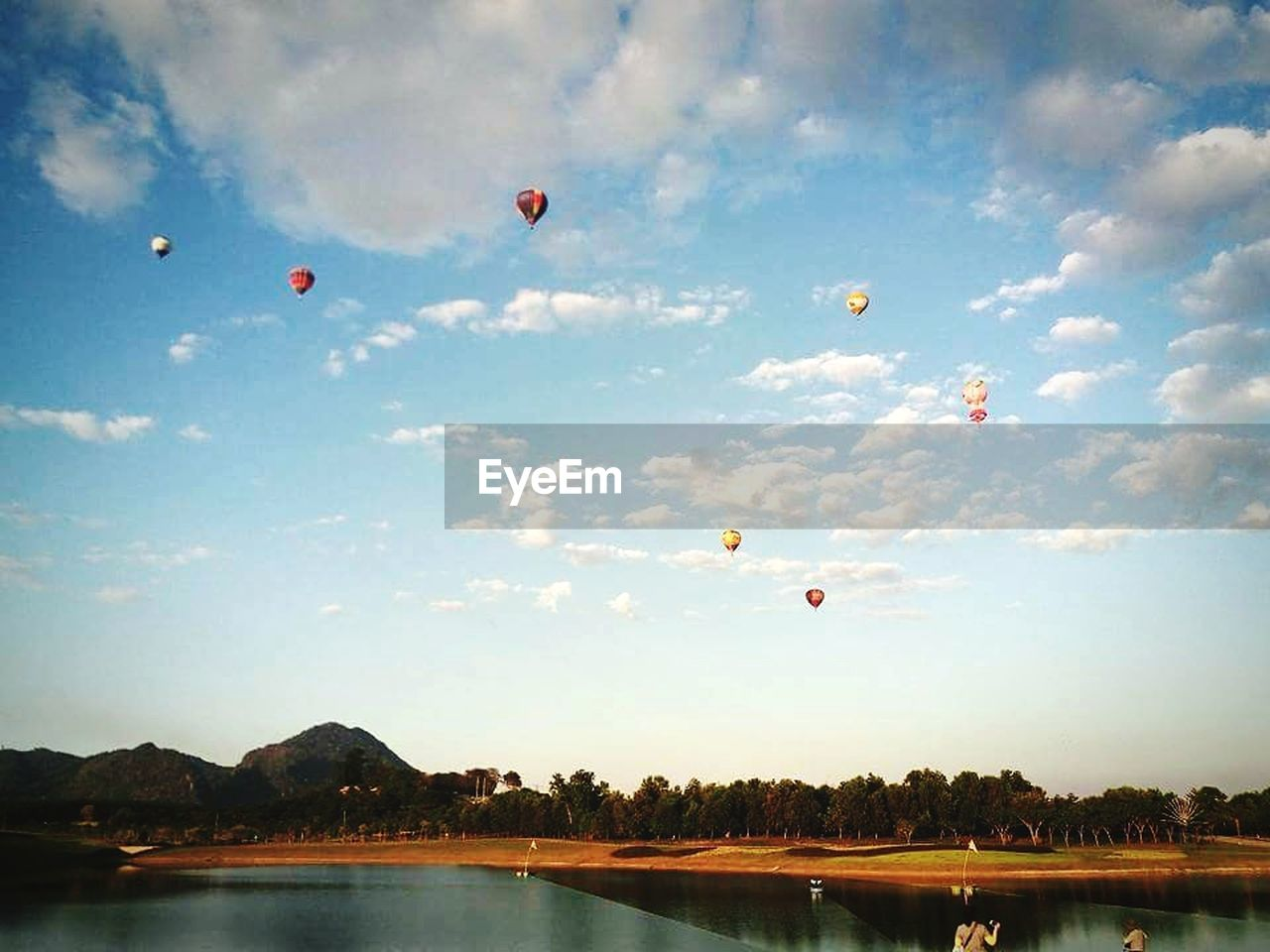 flying, mid-air, sky, adventure, hot air balloon, parachute, leisure activity, outdoors, water, nature, day, scenics, extreme sports, no people, ballooning festival, paragliding