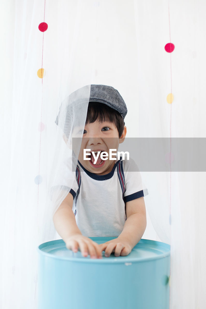 Portrait Of Cheerful Boy Screaming While Standing By Curtains At Home
