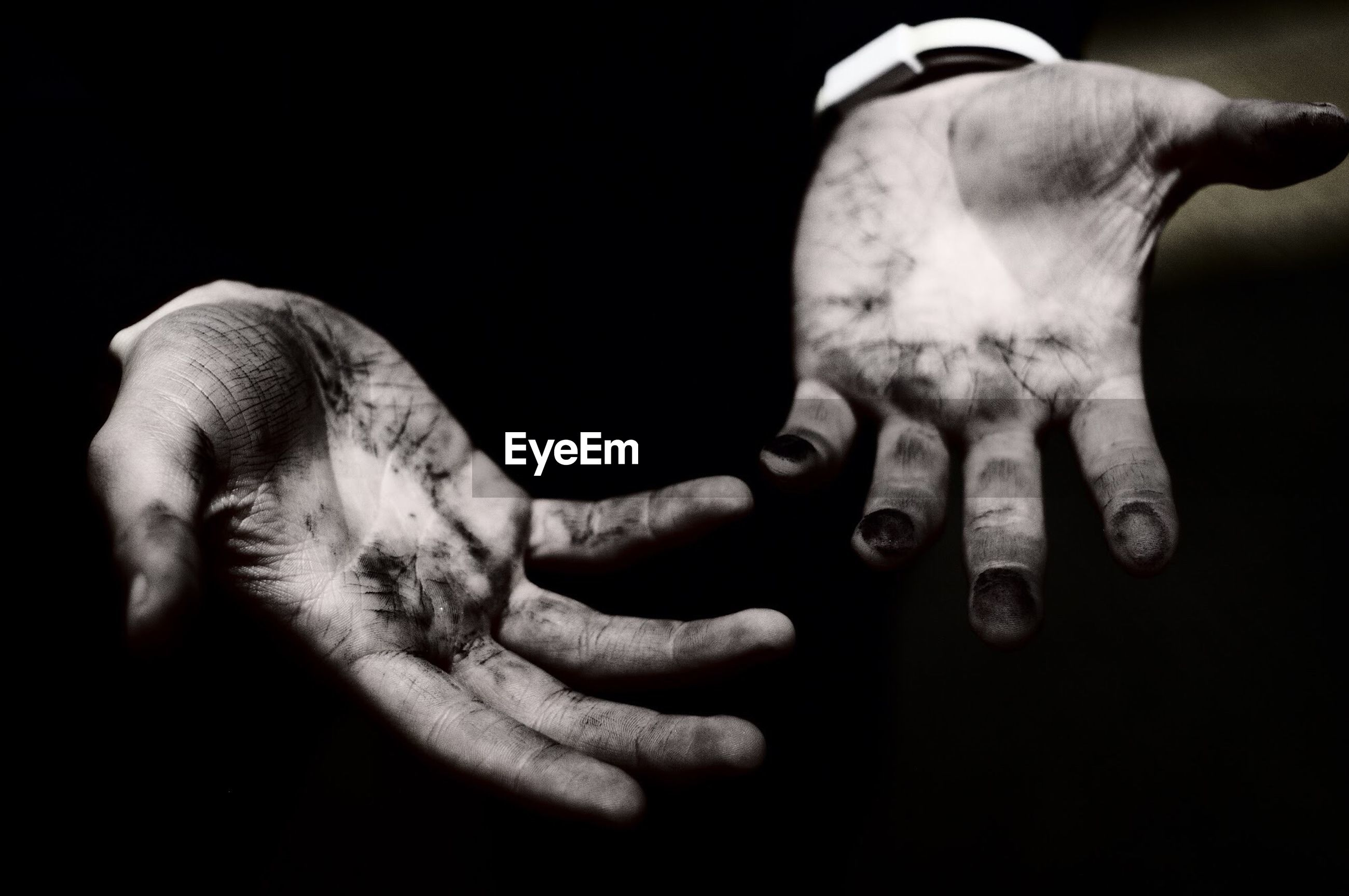 CLOSE-UP OF MAN HAND WITH BLACK BACKGROUND