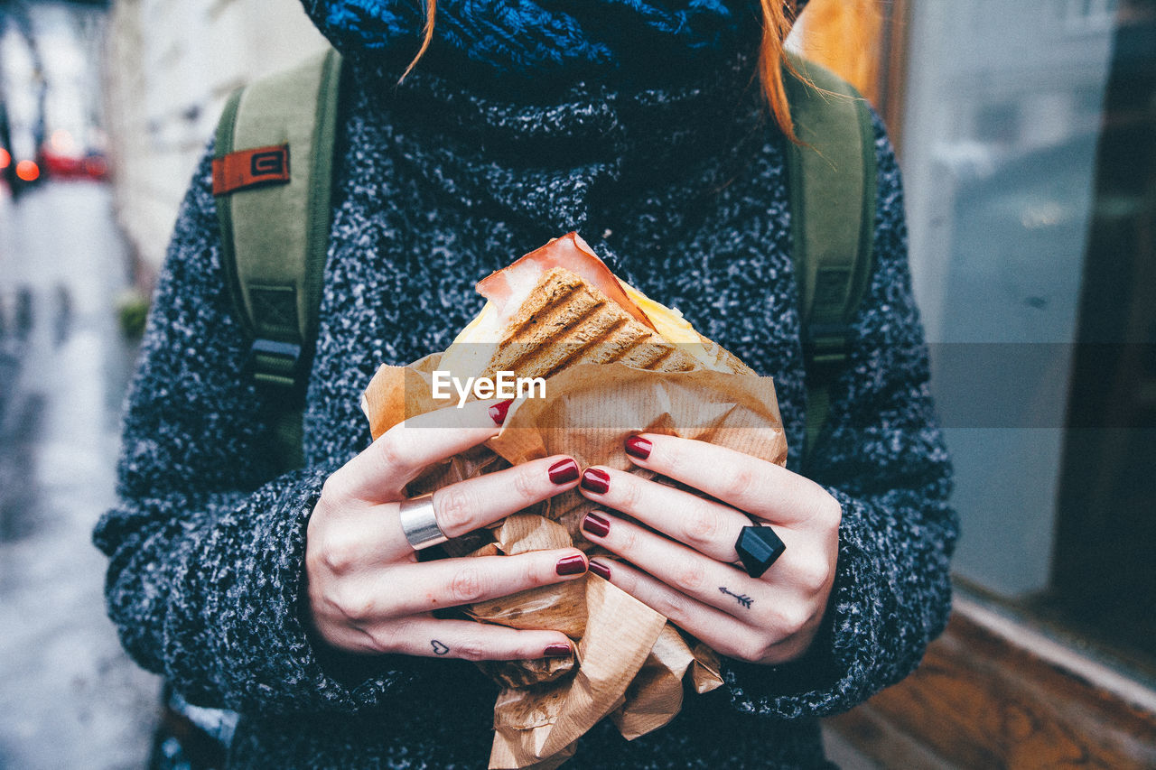 Midsection Of Woman Holding Sandwich