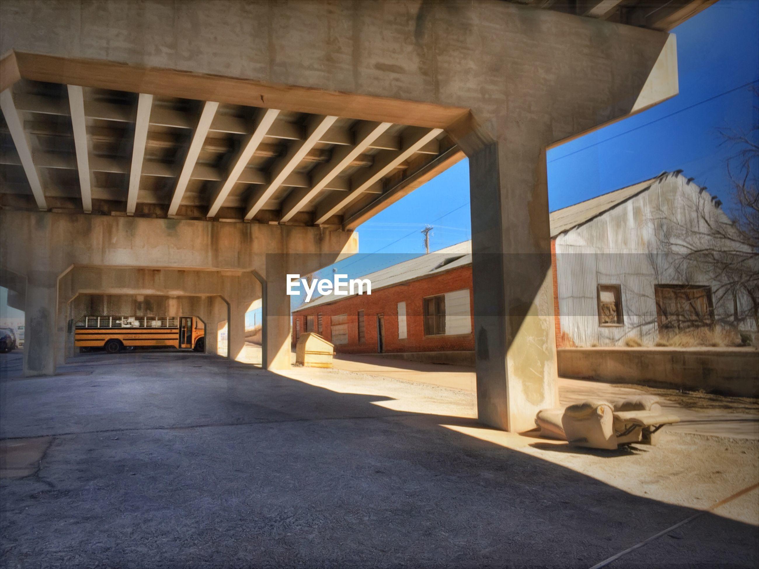 School bus parked under bridge